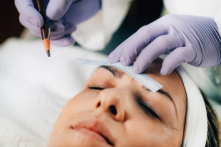 Beautician Addressing the Shape of the Brows Before Microblading.  Semi-Permanent Makeup