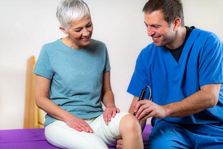 Fisioterapia con láser. Fisioterapeuta que trata la rodilla de una mujer mayor en una clínica