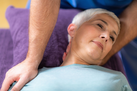 Physical Therapist Stretching Senior Woman's Neck
