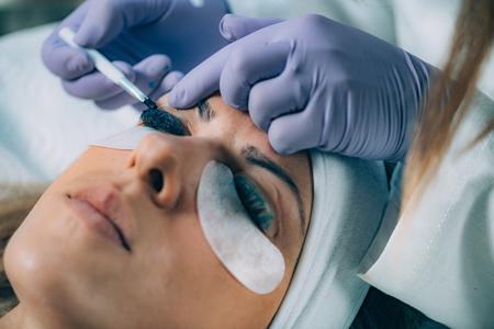 Cosmetologist Puts Black Paint on the Eyelashes During Lash Lifting Procedure. Laminating Eyelashes.
