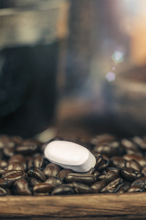Caffeine pill and roasted coffee beans with grounded coffee in wooden bowl in background