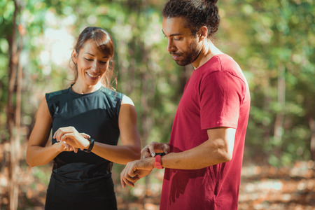 Young couple checking progress on their smart watches after outdoor training Banco de Imagens