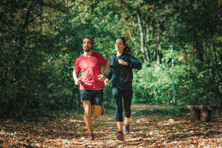 Young Couple Jogging Outdoors in Park. Nature, green background.