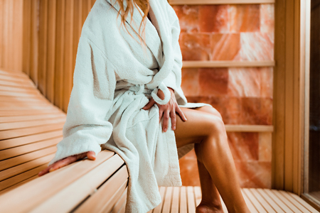 Woman Relaxing in Salt Room. Sitting in Bathrobe and Enjoying .