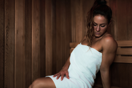Woman with Towel Sitting on a Bench and Relaxing in Hot Sauna. Banco de Imagens