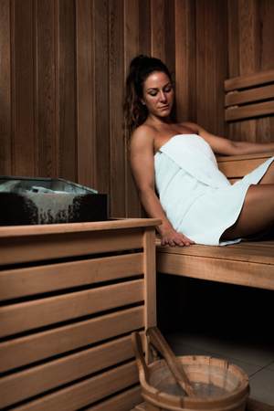 Woman Relaxing in Hot Sauna.