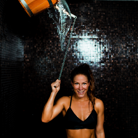 Beautiful Woman Having an Ice Cold Shower Bucket after Sauna. Banco de Imagens