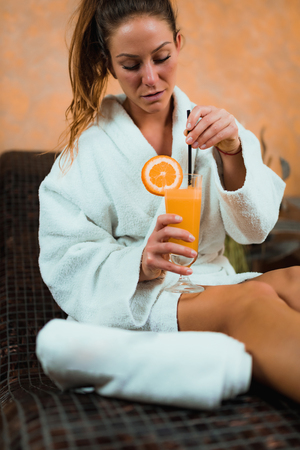 Woman in Bathrobe Sitting on Tepidarium Bed and Drinking Lemonade.
