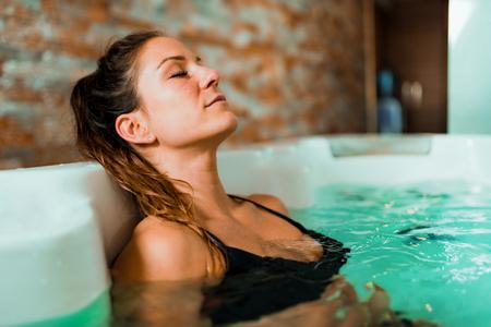 Hermosa mujer disfrutando de bañarse en el centro de spa. Foto de archivo