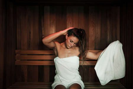 Woman Sitting and Relaxing in Hot Sauna.