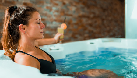 Beautiful Woman Enjoying Jacuzzi in Spa Center. Drinking Lemonade and Relaxing.