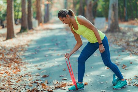 Woman Exercising with Elastic Resistance Band in the Park Stock Photo