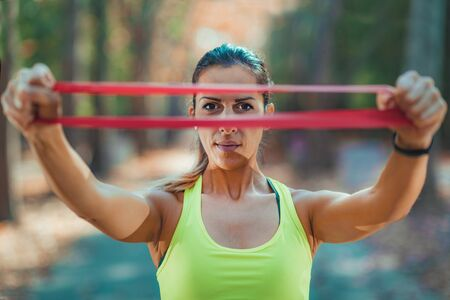 Woman Exercising with Resistance Band Outdoors Stock Photo
