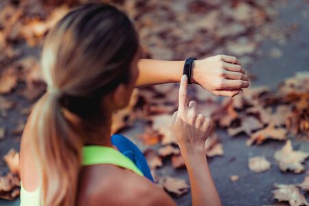 Woman Checking Progress on Smart Watch after Outdoor Training