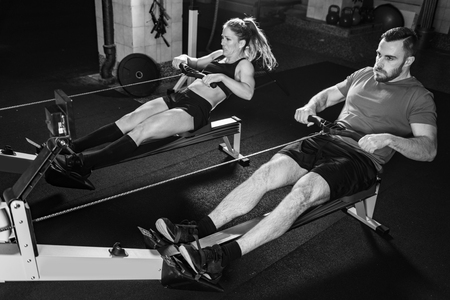 Cross training. Young athletes exercising on rowing machine Foto de archivo