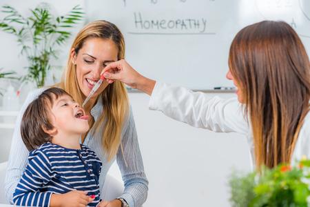 Homeopatía. Madre y niño visitando a un homeópata