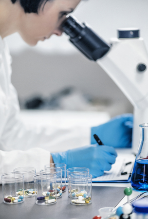 Medical researcher examining a new medicine. Female science student dressed in white lab coat looking through the microscope