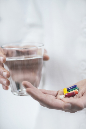 Doctor`s hand holding colorful pills and glass of water