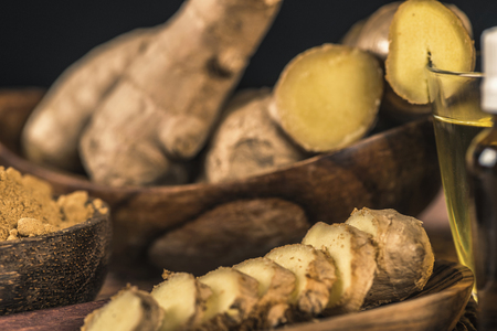 Sliced ginger root and ginger powder in the bowl on the table. Anti-inflammatory herbal medicine Archivio Fotografico