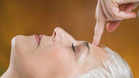 Terapia Facial Ayurveda Marma. Marma terapeuta curando al paciente Sthapani marma, ubicado entre las cejas. Hermosa mujer mayor acostada con los ojos cerrados disfrutando del tratamiento. Chakra del tercer ojo de acupresión. Foto de archivo