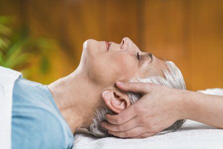 Marma-Therapie. Schöne ältere Frau, die auf Massagetisch liegt und Ayurveda-Gesichtsbehandlung genießt.
