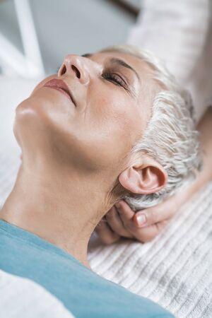 Terapia Marma. Hermosa mujer mayor acostada en la mesa de masajes y disfrutando del tratamiento de Ayurveda, Krikatika marma point.