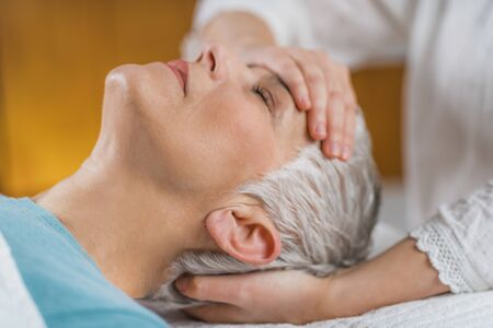 Marma therapy.  Beautiful senior woman lying on massage table and enjoying Ayurveda Facial treatment.