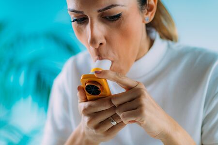 Woman using Spirometer, Measuring Lung Capacity and Force Expiratory Volume