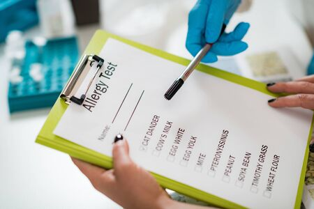 Immunology Doctor Looking at a List With Allergens