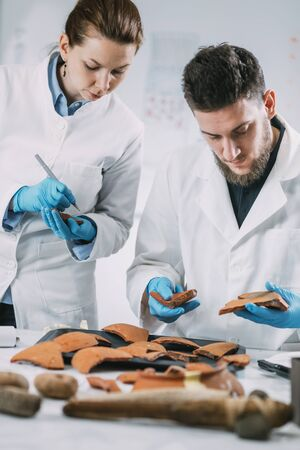 Archeology scientists reconstruct broken pottery in laboratory. Archivio Fotografico