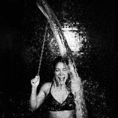 Donna nel centro benessere, facendo una doccia fredda dal secchiello del ghiaccio dopo la sauna.