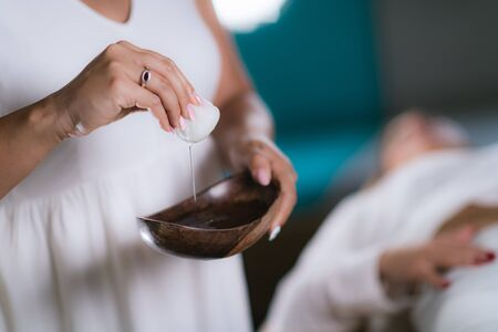 Philippine Psychic Surgery Healer Preparing for Treatment. Using Cotton Ball and Water in Wooden Bowl. Stock fotó