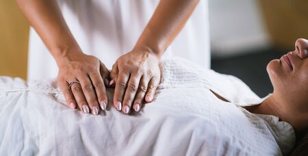 Female Therapist Performing Reiki Therapy Treatment. Hands Over Womans Stomach. Alternative Therapy Concept, Stress Reduction and Relaxation. Stock fotó