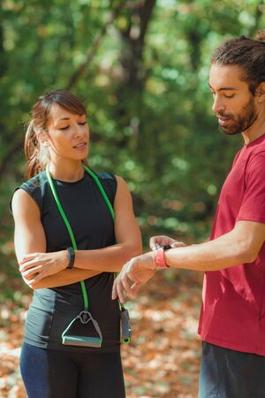 Friends checking progress on their smart watches after outdoor training