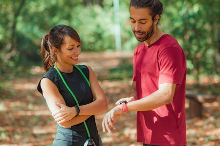 Young couple checking progress on their smart watches after outdoor training Stock Photo