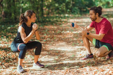Young Couple Exercising with Elastic Resistance Band Outdoors in the Park