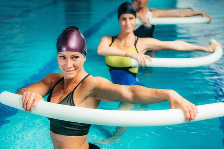 Aqua Aerobic Training with Water Fitness Equipment. Women Training with Swimming Noodles. 版權商用圖片