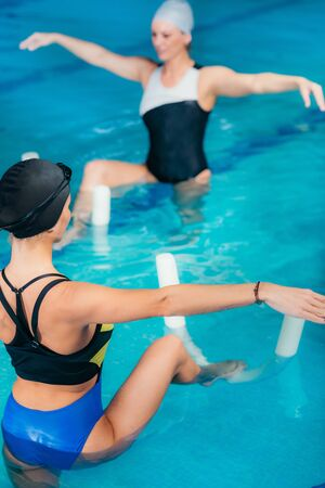 Group of Women with Female Instructor, Water Aerobics Class. 免版税图像