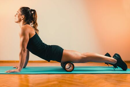 Sporty Woman Massaging Quadriceps with Foam Roller