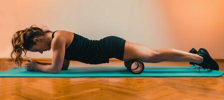 Sporty Woman Massaging Quadriceps with Foam Roller