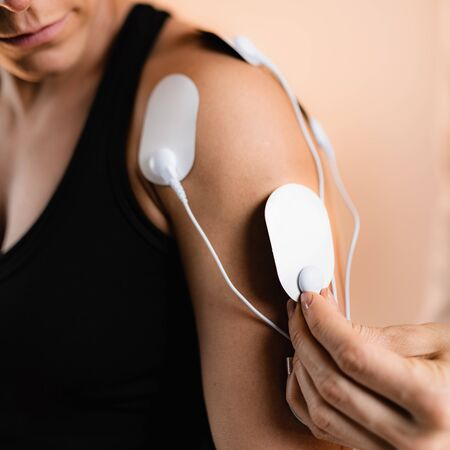 Shoulder Physical Therapy with TENS Electrode Pads, Transcutaneous Electrical Nerve Stimulation. Therapist Positioning Electrodes onto Patients Shoulder