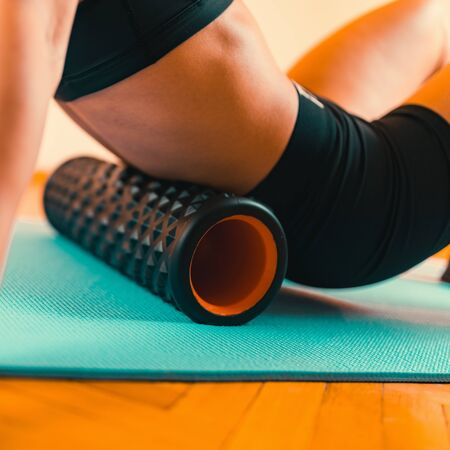 Attractive Female Athlete Stretching Back with Foam Roller