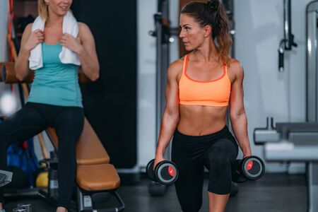 Female Athlete Doing Lunges with Weights in The Gym
