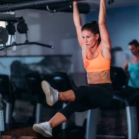 Female Athlete Doing Pull-Ups in The Gym 写真素材