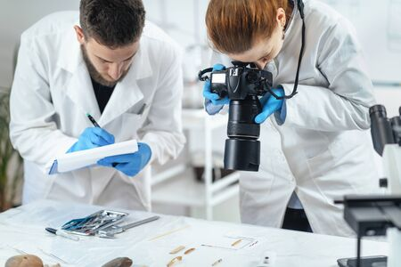 Young archaeology researchers document lithics with camera in laboratory. 스톡 콘텐츠