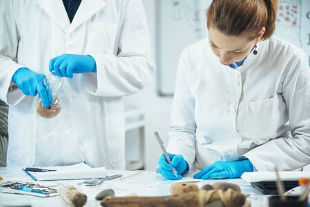 Male archaeologist putting ancient weight in a plastic bag, female archaeologist marking prehistoric artifact with serial number.