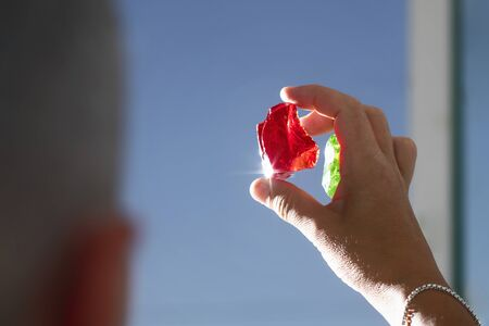 Female crystal healer holding red Andara crystal against sun and blue sky. Cleansing and charging crystals