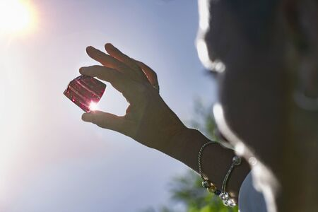 Female crystal healing therapist hands holding purple amethystine quartz crystal against sun and blue sky. Cleansing and charging crystals