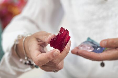 Female crystal healer holding red andara crystal. Alternative medicine concept.