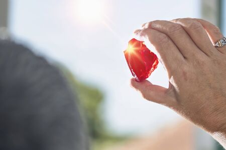 Female crystal healer holding red Andara crystal against sun and blue sky. Cleansing and charging crystals 写真素材